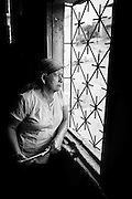 """2015/03/13 - Pile, Ecuador: Mariana Rivera, 73, looks outside her window in order for time to pass.  She is only able to work between 6am to 9am and then from 7pm till 10pm, because it is when the humidity conditions are at its best to work on the straw. Otherwise the heat will dry the straw and break it, damaging the hat.  UNESCO declared the """"Montecristi hat"""" in 2012 as Intangible Cultural Heritage of Humanity."""