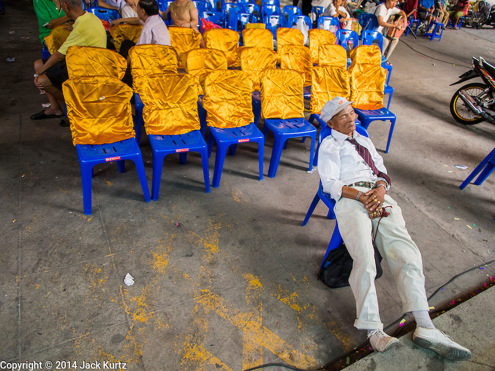 27 SEPTEMBER 2014 - BANGKOK, THAILAND: A man naps during the celebration of the Vegetarian Festival at the Chow Su Kong Shrine in Talat Noi, a Chinese enclave in Bangkok. The Vegetarian Festival is celebrated throughout Thailand. It is the Thai version of the The Nine Emperor Gods Festival, a nine-day Taoist celebration beginning on the eve of 9th lunar month of the Chinese calendar. During a period of nine days, those who are participating in the festival dress all in white and abstain from eating meat, poultry, seafood, and dairy products. Vendors and proprietors of restaurants indicate that vegetarian food is for sale by putting a yellow flag out with Thai characters for meatless written on it in red.    PHOTO BY JACK KURTZ