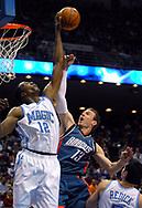 Orlando Magic center Dwight Howard, left, blocks a shot by Charlotte Bobcats guard Matt Carroll as J.J. Redick watches during the first half of their basketball game in Orlando, Florida.