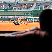 PARIS, FRANCE May 29. A ball boy watches from the pit window as Johanna Konta of Great Britain falls while playing against Lauren Davis of the United States on Court One in the Women's Singles second round match at the 2019 French Open Tennis Tournament at Roland Garros on May 29th 2019 in Paris, France. (Photo by Tim Clayton/Corbis via Getty Images)