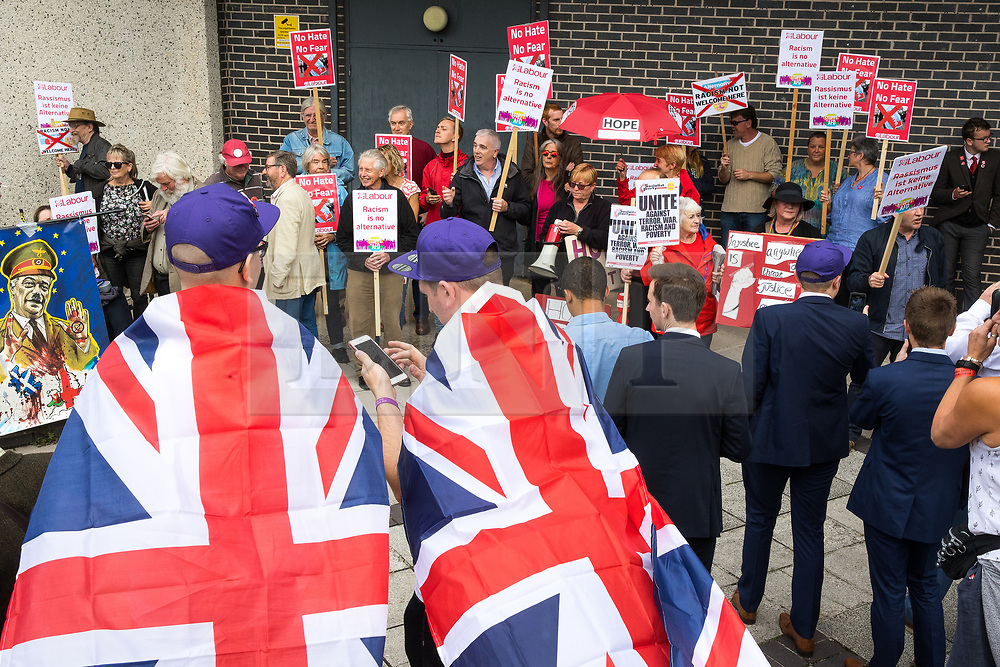 © Licensed to London News Pictures . 29/09/2017 . Torquay , UK . UKIP supporters wearing Union Jack flag capes watch protesters , including one carrying a banner featuring Nigel Farage as Adolf Hitler , outside the venue . The UK Independence Party Conference at the Riviera International Centre . UKIP is due to announce the winner of a leadership election which has the potential to split the party . Photo credit: Joel Goodman/LNP