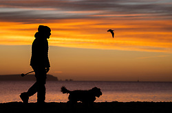 © Licensed to London News Pictures. 01/12/2020. Mudeford, UK. A man walks his dog on the sea front at Mudeford in Dorset as the winter sun illuminates the clouds above The Needles on The Isle of Wight. Most of England is experiencing low temperatures and clear skies today on the first day of the Meteorological winter. Photo credit: Peter Macdiarmid/LNP