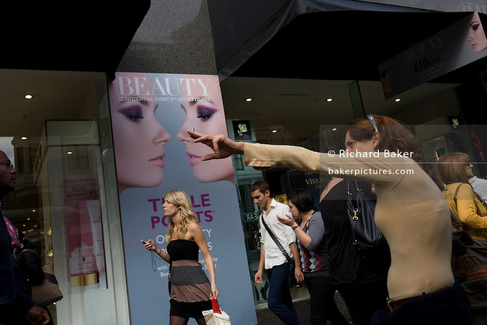 A Beauty ad with smoking woman pointing in a west end window.
