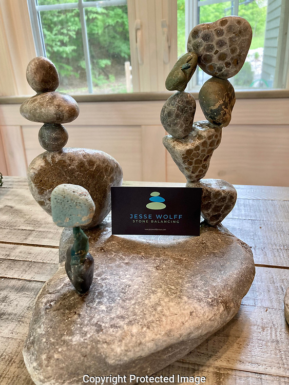 """These sculptures are completely comprised of rocks found on Lake Michigan beaches in the Grand Traverse region.  Each includes at least both a Petoskey and a Leland """"Blue"""" stone. <br /> <br /> Creative Process:  (1) Each stone is balanced on another and must remain in this natural equilibrium for 30 minutes. (2) Next, I remove the stone and apply an adhesive to the balance point. (3) I then re-balance the stone on the wet glue and let it air dry (without clamps, holding, support of any kind).<br /> <br /> My perspective:  Learning to patiently balance glacially created stones in a composed state of natural equilibrium speaks to me. Metaphorically, it is a reminder that we all need touchpoints (in rock balancing there are three) for balance in our lives. When the essential balancing points are found, our resistance disappears, and, least for a time, natural stasis occurs."""