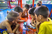 """18 DECEMBER 2104 - BANGKOK, THAILAND: Boys who want to become boxers drink energy drinks and watch videos on a smart phone at the Kanisorn gym. The Kanisorn boxing gym is a small gym along the Wong Wian Yai - Samut Sakhon train tracks. Young people from the nearby communities come to the gym to learn Thai boxing. Muay Thai (Muai Thai) is a Thai fighting sport that uses stand-up striking along with various clinching techniques. It is sometimes known as """"the art of eight limbs"""" because it is characterized by the combined use of fists, elbows, knees, shins, being associated with a good physical preparation that makes a full-contact fighter very efficient. Muay Thai became widespread internationally in the twentieth century, when practitioners defeated notable practitioners of other martial arts. A professional league is governed by the World Muay Thai Council. Muay Thai is frequently seen as a way out of poverty for young Thais and Muay Thai camps and schools are frequently crowded. Muay Thai professionals and champions are often celebrities in Thailand.     PHOTO BY JACK KURTZ"""
