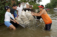 Maritza Saucedo,from left, Lupe Delarosa, Peter Lawrence and Brian Vazquez, right struggle with a shopping cart full of sand bags outside their homes on Dee Road in Des Plaines, Ill. on Thursday, Aug. 22, 2002 in an attempt to prevent more water from infiltrating their homes.  (AP)