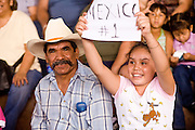 July 13, 2008 -- PHOENIX, AZ: Young Lucha Libre fans show their support for their favorite Lucha Libre characters during a show at El Gran Mercado in Phoenix. Lucha Libre is Mexican style wrestling. There are heros (Tecnicos) and villians (Rudos). The masks are popular as children's gifts and tourist mementos. As the size of the Mexican community in the Phoenix area has grown, attendance at the Lucha Libre shows has increased. Lucha Libre differs from American style entertainment wrestling in several ways, but principally the wrestlers are more acrobatic and rely less on body slams than American wrestling. The shows, which used to be held only periodically, are now held every week at El Gran Mercado, a flea market and swap meet that caters mostly to the Mexican community in Phoenix.   Photo by Jack Kurtz / ZUMA Press