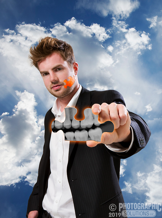 A man holding a puzzle piece with an xray of his own teeth