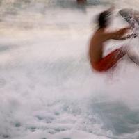 Waimea Bay scene, skim boarder in wave, motion blur