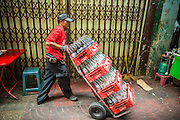"""06 MARCH 2013 - BANGKOK, THAILAND:  A soft drink delivery man on his rounds in Bangkok. Thailand's economic expansion since the 1970 has dramatically reduced both the amount of poverty and the severity of poverty in Thailand. At the same time, the gap between the very rich in Thailand and the very poor has grown so that income disparity is greater now than it was in 1970. Thailand scores .42 on the """"Ginni Index"""" which measures income disparity on a scale of 0 (perfect income equality) to 1 (absolute inequality in which one person owns everything). Sweden has the best Ginni score (.23), Thailand's score is slightly better than the US score of .45.  PHOTO BY JACK KURTZ"""