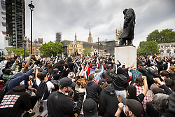 © Licensed to London News Pictures. 03/06/2020. London, UK. Members of the campaign group Black Lives Matter and supporters, take the knee below the statue of wartime leader Winston Churchill as they gather in Parliament Square in central London following the death of African American George Floyd while in police custody. The death of George Floyd, who died after being restrained by a police officer In Minneapolis, Minnesota, has caused widespread rioting and looting across the USA. Photo credit: Peter Macdiarmid/LNP