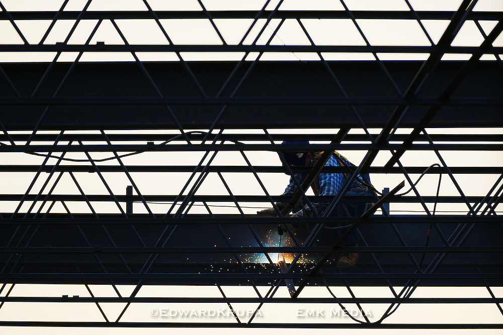 An ironworker welding the steel framework of a building.
