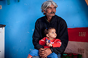"Rudolf (52) with his granddaughter in their selfconstructed house. After one year of contruction (04/2014) the family is already able to life in the building. They are with their families among those who joined the micro loan program in Rankovce. ""They and their son Rudo and three small grandchildren have never lived in their own home. They have been homeless or lived in a caravan without drinking water and electricity. Since the fall of communism Rudolf has not been able to get a permanent job."
