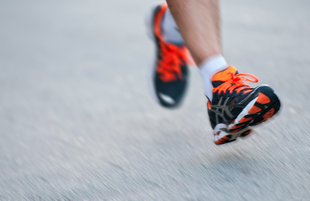 Close up of runner legs in motion. Motion blur effect, space for copy.