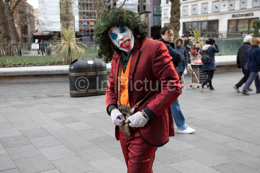 Man dressed up as a Joker type character with rotten teeth, stalks around on Leicester Square trying to scare passers by  in London, United Kingdom.