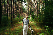 """MERIDIAN, MS – AUGUST 3, 2018: Clayton George, 57, walks under a canopy of mature Loblolly pine with his dog, Poupon. As a resident of Tennessee, George makes the four hour drive south every two weeks to check on his family's 400 acre tract, and visit his father who still lives there.<br /> <br /> In 1987, George and a friend walked in rows planting the family's first batch of Loblolly pine, where soybeans, wheat and cattle once covered the family's 400 acres.  The shift to timber was largely prompted by the Conservation Reserve Program, a popular new farm subsidy in the 1980s that encouraged farmers to reforest depleted land by paying them for every acre of trees planted. Since 1926, the George family had made a good living from their eastern Mississippi farm, but the decline of soybeans and other crops eventually led George to consider growing trees instead –a crop that landowners throughout the south believed would bring in easy money. Thirty years later, however, the same landowners are now facing unexpected financial hardship. Stumpage prices have been on a steady decline – as much as 45% since 2007 – and landowners are rethinking timber as a worthwhile investment. """"""""We figured we''d plant trees and come back and harvest it in 30 years, and in the meantime go into town to make a living doing something else,"""" George said. As co-owner of the family acreage with three other family members, George always considered himself the most nostalgic Now, as he patiently awaits for right time to harvest a 30 year investment, even he considers the future of the land uncertain. CREDIT: Bob Miller for The Wall Street Journal<br /> TIMBER_AL"""
