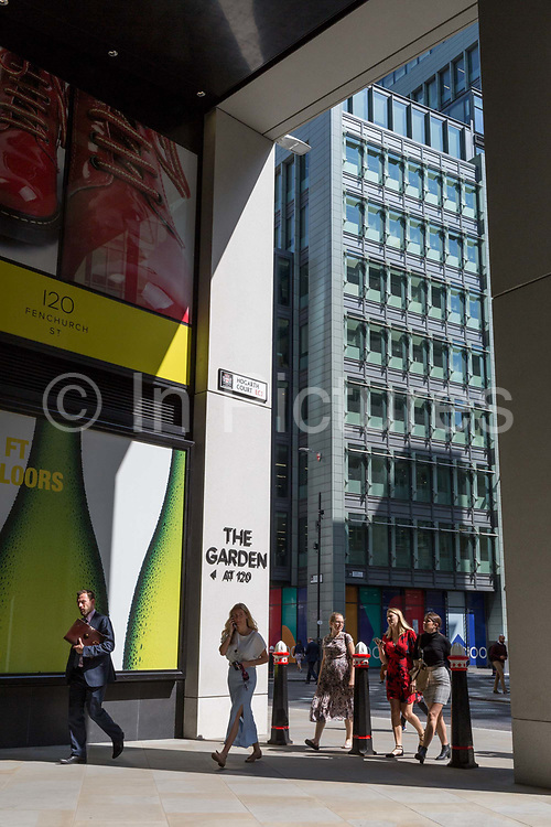 City workers pass through the latest architecture of Fen Court aka Hogarth Court on Fenchurch Street in the City of London, the capitals financial district aka the Square Mile, on 22nd August 2019, in London, England.