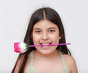 happy Young girl of 9 with a flower in her mouth Model release available