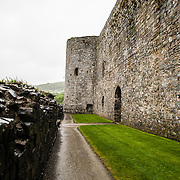 Ground-level view of the heavily fortified walls at Harlech Castle in Harlech, Gwynedd, on the northwest coast of Wales next to the Irish Sea. The castle was built by Edward I in the closing decades of the 13th century as one of several castles designed to consolidate his conquest of Wales.