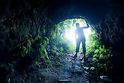 Silhouette of a person exploring a tunnel made in WWII for the storing of supplies for Japanese Troops
