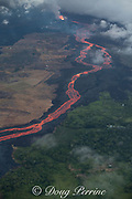 Aerial view of Kilauea Volcano east rift zone erupting hot lava from Fissure 8 in Leilani Estates subdivision near the town of Pahoa. The lava drains downhill as an incandescent river to Kapoho, Puna District, Hawaii Island ( the Big Island ), Hawaiian Islands, U.S.A. Land at lower right is swept by fresh trade winds, so vegetation is alive. Wind carries toxic fumes from lava river across to left, so vegetation on that side is mostly dead.