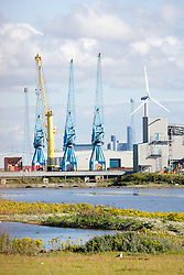 Shipyard cranes and wind turbine at the Liverpool docks area North West England,