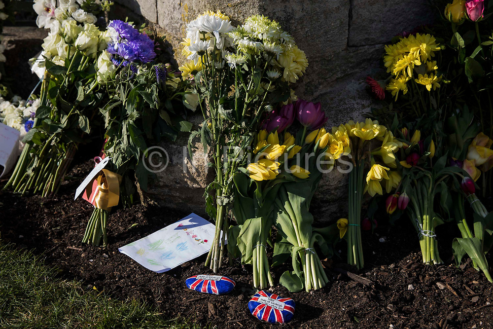 Floral tributes and pebbles painted with a Union Jack design left by members of the public outside the Cambridge Gate to Windsor Castle are pictured on the eve of the funeral of the Duke of Edinburgh on 16th April 2021 in Windsor, United Kingdom. The funeral of Prince Philip, Queen Elizabeth II's husband, will take place at St Georges Chapel in Windsor Castle at 15:00 BST on 17th April, with the ceremony restricted to 30 mourners in accordance with current coronavirus restrictions.