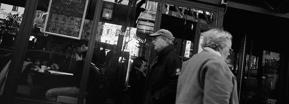 Street Scene on Boulevard de Grenelle as individuals walk past a cafe  in Paris, France. October 21, 2007. Photo Tim Clayton..Paris is often known as 'The City of Love' but like any major City in the world, the inhabitants often live a singular existence, going about their daily lives in relative solitude. Parisians are respectful of each others space, often courteous and polite while extremely conscious of their own image. While love can be seen openly around the streets of Paris, so can the separate lives of Parisians.