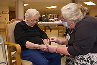 Betty Young gets a manicure by Suzanna, one of the volunteers with Belknap County Nursing Home on Tuesday.  (Karen Bobotas/for the Laconia Daily Sun)