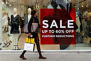 A woman with shopping bags walks past a 60% off sale sign in a shop window in Oxford Street, London, UK on January 03, 2019