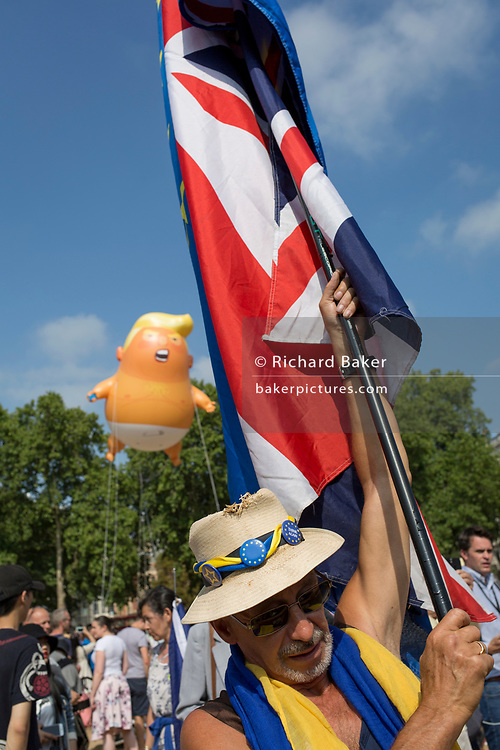 London, UK: The inflatable balloon called Baby Trump flies above a Brexit protestor and the British Union Jack flag Parliament Square in Westminster, the seat of the UK Parliament, during the US President's visit to the UK, on 13th July 2018, in London, England. Baby Trump is a 20ft high orange blimp depicting the US President as an enraged, smartphone-clutching infant - and given special permission to appear above the capital by London Mayor Sadiq Khan because of its protest rather than artistic nature. It is the brainchild of Graphic designer Matt Bonner. Photo by Richard Baker / Alamy Live News