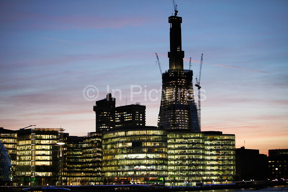 Office buildings at More London lit up at night in front of The Shard, which is under construction and silhouetted in the evening sunset sky. This new business district ha glass sided offices which revela the levels of each floor and the business that goes on within each glowing space.