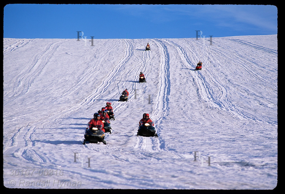 Snowmobilers race down slope atop Vatnajokull glacier during a two-hour Glacier Tours trip; southeast Iceland.