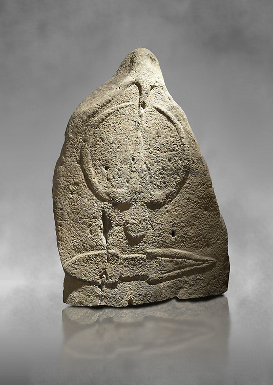 Late European Neolithic prehistoric Menhir standing stone with carvings on its face side. The representation of a stylalised male figure starts at the top with a long nose from which 2 eyebrows arch around the top of the stone. below this is a carving of a falling figure with head at the bottom and 2 curved arms encircling a body above. at the bottom is a carving of a dagger running horizontally across the menhir.  From Barrili I site, Laconi. Menhir Museum, Museo della Statuaria Prehistorica in Sardegna, Museum of Prehoistoric Sardinian Statues, Palazzo Aymerich, Laconi, Sardinia, Italy .<br /> <br /> Visit our PREHISTORIC PLACES PHOTO COLLECTIONS for more photos to download or buy as prints https://funkystock.photoshelter.com/gallery-collection/Prehistoric-Neolithic-Sites-Art-Artefacts-Pictures-Photos/C0000tfxw63zrUT4