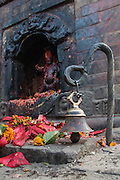Nepal, Kathmandu, Pashupati Temple, Hindu deity, there is a stone carving is in the background, along with some offersing of flowers. In the foreground is a small bell.