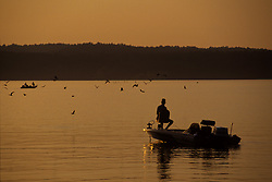 Serene sunset silhouette of a fisherman sitting in his boat fishing on Toledo Bend lake at sunset.