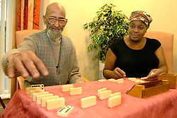 An elderly sikh man plays dominoes with a Care Assistant in a  multi-cultural elderly people's  Day Centre