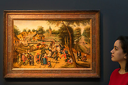 """© Licensed to London News Pictures. 02/12/2016. London, UK. A staff member views """"Return of the Kermesse"""" by Pieter Breughel the Younger (est. GBP 2-3m), at a preview of Sotheby's upcoming Old Masters Evening Sale in New Bond Street. Photo credit : Stephen Chung/LNP"""