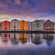 www.aziznasutiphotography.com              Trondheim with picturesque, tiny, wooden houses. This idyllic neighbourhood on the east side of the Nidelva river features old timber buildings, originally the homes of the working class. Now restored, Bakklandet is a charming mixture of houses, shops and cafés.<br /> Nidelva river cuts through the city, winding its way along the Nidarosdomen park and picturesque areas, with the historic, wooden wharf houses lining its sides towards the mouth at the Trondheim fjord, and the beautiful, wooden bridge amle Bybrocrossing the river.