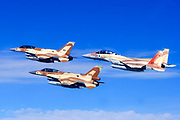 A formation of 2 F-16 and one F-15 Israeli Air Force fighter jets on a blue sky background
