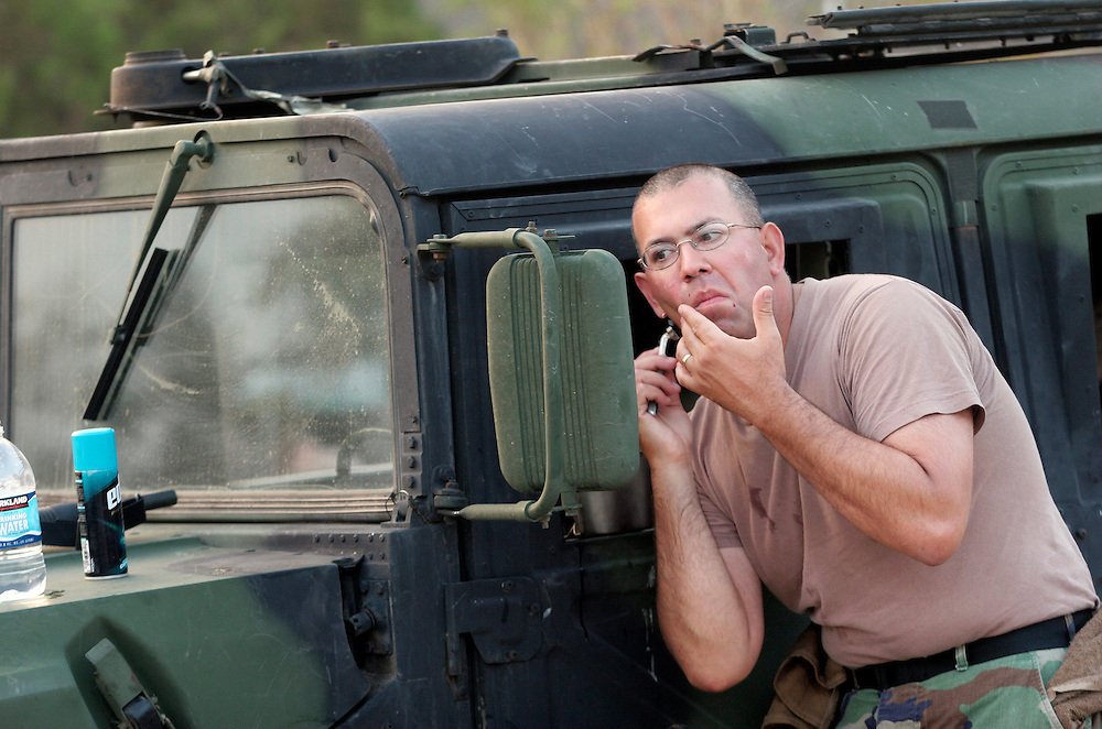 """Staff Sgt. """"Mac"""" McIntosh, from Monmouth, uses a Humvee mirror to check the progress of his morning shave. Oregon National Guard troops work in New Orleans after the wrath of Hurricane Katrina. Photographed September 10, 2005. (Thomas Patterson / Statesman Journal)"""