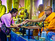 "24 JUNE 2017 - BANG KRUAI, NONTHABURI: A Buddhist monk gives a prayer bracelet to a woman after a rebirthing ceremony at Wat Ta Kien (also spelled Wat Tahkian), a Buddhist temple in the suburbs of Bangkok. People go to the temple to participate in a ""Resurrection Ceremony."" Thai Buddhists believe that connecting people by strings around their heads, which are connected to a web of strings suspended from the ceiling, amplifies the power of the prayer. Groups of people meet and pray with the temple's Buddhist monks. Then they lie in coffins, the monks pull a pink sheet over them, symbolizing their ritualistic death. The sheet is then pulled back, and people sit up in the coffin, symbolizing their ritualist rebirth. The ceremony is supposed to expunge bad karma and bad luck from a person's life and also get people used to the idea of the inevitability of death. Most times, one person lays in one coffin, but there is family sized coffin that can accommodate up to six people. The temple has been doing the resurrection ceremonies for about nine years.     PHOTO BY JACK KURTZ"