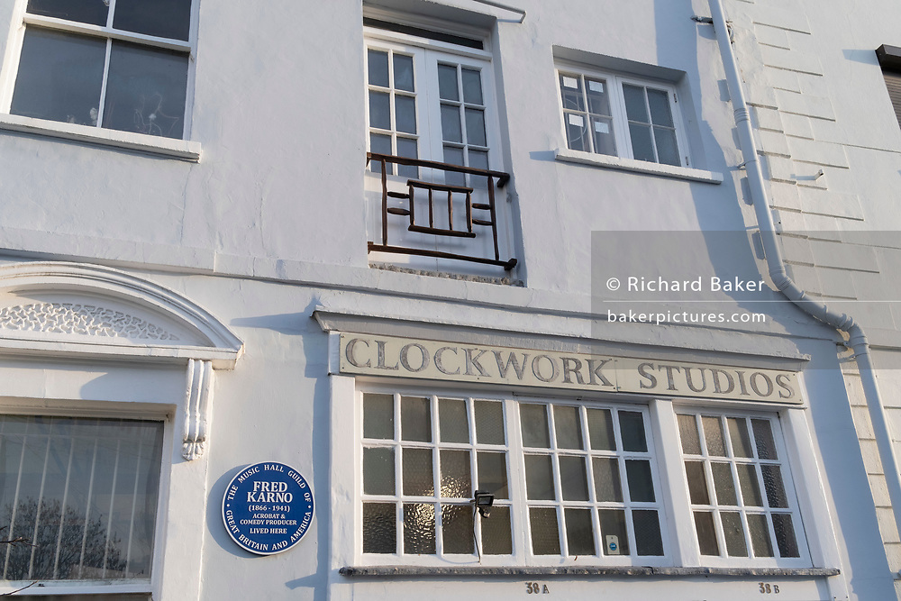 "An exterior of Clockwork Studios on Southwell Rd, in Brixton, south London, on 11th February 2021, in London, England. Clockwork Studios currently houses over 20 diverse independent art businesses but once accomodated comedians and clock makers. At the turn of the 20th century the ""Fun Factory"", as it was then known, was home to Fred Karno's Vaudeville theatre group. Silent movie stars Charlie Chaplin and Stan Laurel, two of Karno's most notable performers would have spent many hours there rehearsing. The Music Hall Guild of Great Britain and America recently fixed a commemorative blue plaque next to the main door to remember the comedy impresario Fred Karno. Also, while still young, future British Prime Minister, John Major lived a few streets away. (Photo by Richard Baker / In Pictures via Getty Images)"