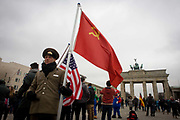 "Actors in US and Soviet army uniforms hold flags to recount German history during the second world war and later, the cold war - beneath the Brandenburg Gate in Unter den Linden in central Berlin, Germany. The site is near the former border between Communist East and West Berlin during the Cold War. Here also, Berlin was separated by the occupying sectors of US, British, French and Soviet forces after WW2. The Berlin Wall was a barrier constructed by the German Democratic Republic (GDR, East Germany) starting on 13 August 1961, that completely cut off (by land) West Berlin from surrounding East Germany and from East Berlin. The Eastern Bloc claimed that the wall was erected to protect its population from fascist elements conspiring to prevent the ""will of the people"" in building a socialist state in East Germany."