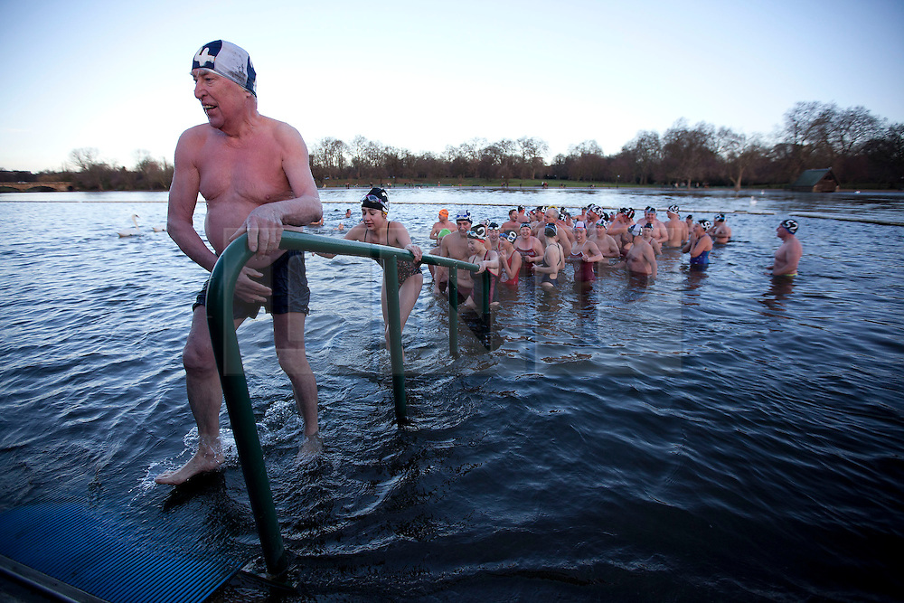 © Licensed to London News Pictures. 25/12/2013. London, UK. Members of the Serpentine Swimming Club queue to leave the water and receive a glass of sherry after the Serpentine Swimming Club's annual Christmas morning 'Peter Pan Cup' race in Hyde Park, London, today (25/12/2013). The race, which takes place every Christmas Day on the Serpentine River, takes its name from from the novel by J.M.Barrie after the author presented the first Peter Pan Cup in 1904. Photo credit: Matt Cetti-Roberts/LNP