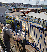 Artist Ben Taffinder painting at Falmouth Docks, Cornwall.