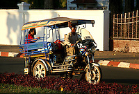 Tuk Tuk at Sunset - An auto rickshaw or three wheelers (tuk-tuk  or auto rickshaw) is one of the chief modes of transport across many parts of Southeast Asia  as a vehicle for hire. It is a motorized version of the traditional rickshaw or velotaxi, a small three-wheeled cart. <br /> Auto rickshaws are popular in many Asian countries such as Laos.