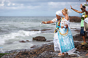 Middle aged Brazilian woman, Bahiana, in traditional Candomble dress of white, praying and making offerings of flowers to the sea in honour of Yemanja. February 2nd is the feast of Yemanja, a Candomble Umbanda religious celebration, where thousands of adherants visit the Rio Vermehlo Red River to pay their respects to Yemanja, the Orixa goddess of the Sea and water.