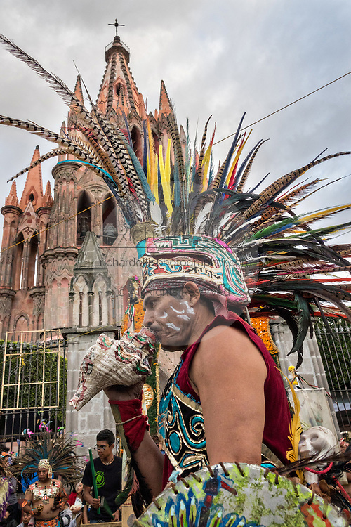 A Mexican Conchero blows a conch shell in a ceremony outside the Parroquia Church of Michael the Archangel during the week long fiesta of the patron saint Saint Michael October 1, 2017 in San Miguel de Allende, Mexico.