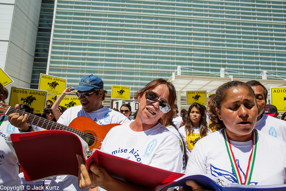 01 AUGUST 2012 - PHOENIX, AZ:    People sing and pray in front of the US Courthouse in Phoenix Wednesday. About 200 people, mostly Latino immigrants' rights and civil rights activists, gathered in front of the Sandra Day O'Connor Courthouse in Phoenix Wednesday to pray on what is expected to be the last day of testimony in the racial profiling trial against Maricopa County Sheriff Joe Arpaio. The suit, brought by the ACLU and MALDEF in federal court against Maricopa County Sheriff Joe Arpaio, alleges a wide spread pattern of racial profiling during Arpaio's ''crime suppression sweeps'' that targeted undocumented immigrants. U.S. District Judge Murray Snow granted the case class action status opening it up to all Latinos stopped by Maricopa County Sheriff's Office deputies during the crime sweeps. The case is being heard in Judge Snow's court.  PHOTO BY JACK KURTZ